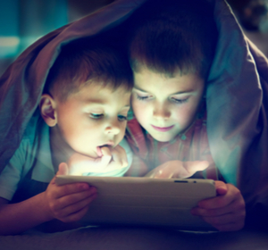 Two boys under blanket looking at tablet